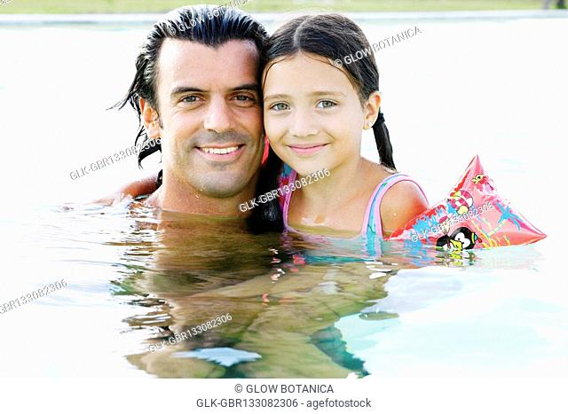 Portrait of a man and his daughter smiling in a swimming pool