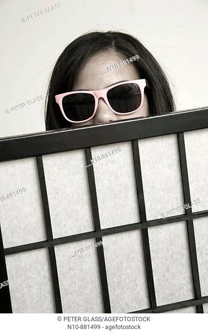 Young woman, wearing sunglasses, looking over the top of a screen