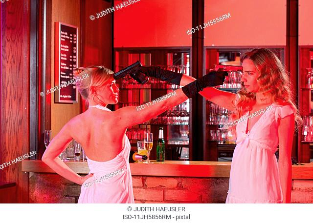 two girls at bar with plastic guns