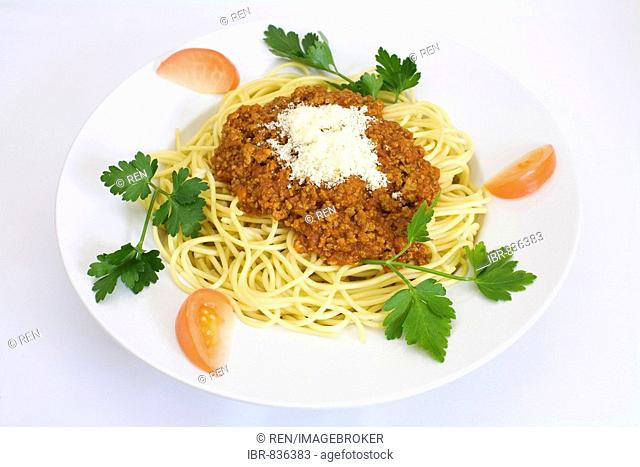 Spaghetti bolognese with parmesan cheese, garnished with tomato wedges and flat leaf parsley