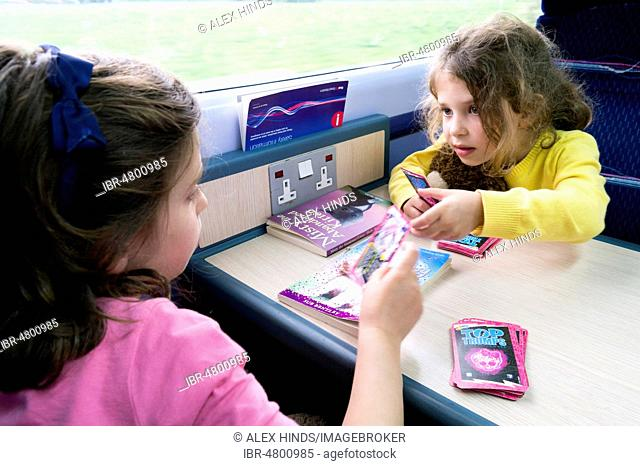 Children playing card game during a train journey, UK