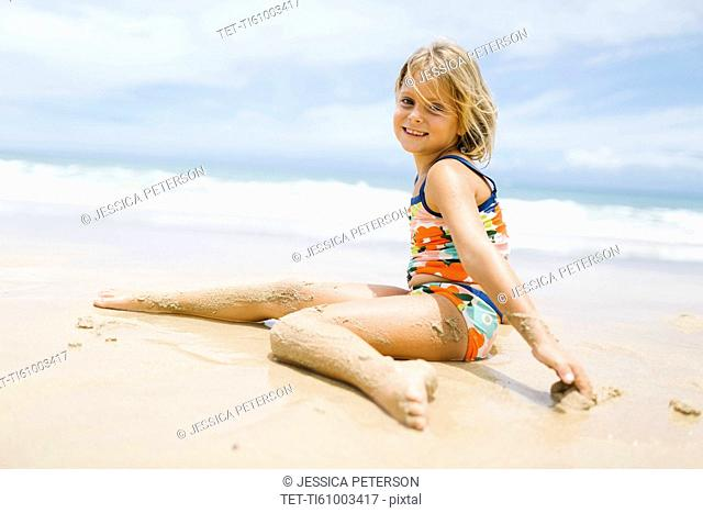 Girl (6-7) sitting on beach