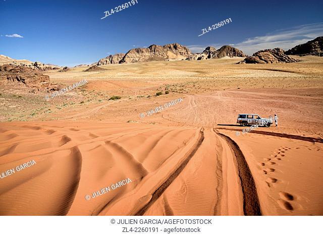 Car on a sand dune, red sand desert and rocks. Jordan, Wadi Rum desert, protected area inscribed on UNESCO World Heritage list. Model Released
