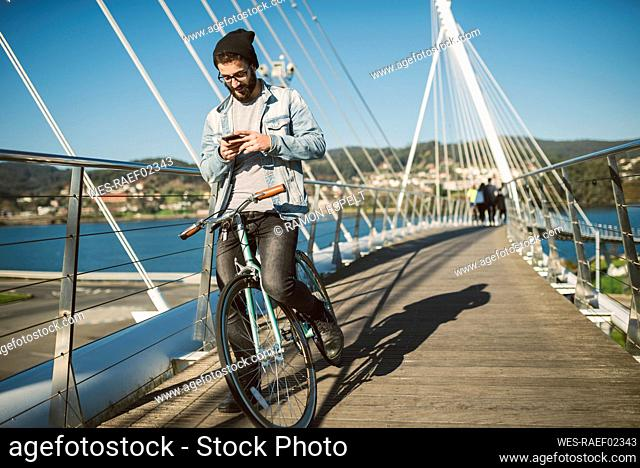 Young man commuting in the city with his fixie bike, using smartphone