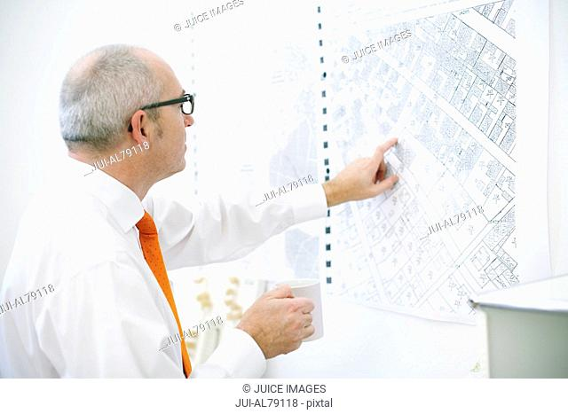Man pointing at map on wall