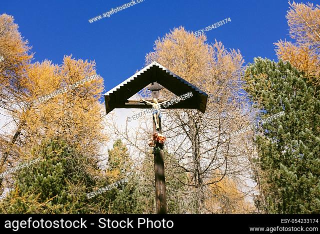 Autumn in the mountains, crucified place in a forest of larch, Valdidentro, Alta Valtellina, Lombardy, Italy