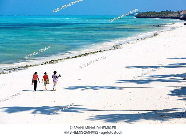 Tanzania, Zanzibar, Jambiani, young women tourists walking on the beach