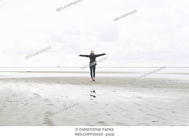 Netherlands, Ouddorp, back view of woman with arms outstretched standing on the beach in autumn