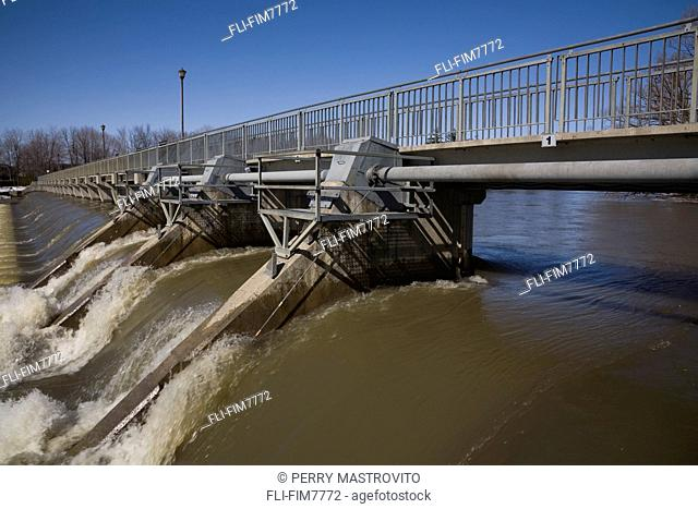 Polluted water through a water flow control gate on the Mille-Iles river in spring, Lanaudiere, Quebec
