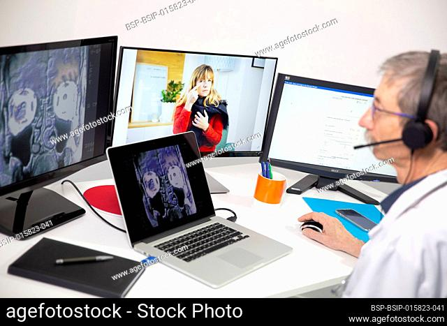 A GP during a video consultation, looking at the x-ray of a woman's sinuses who has a pain in her sinuses