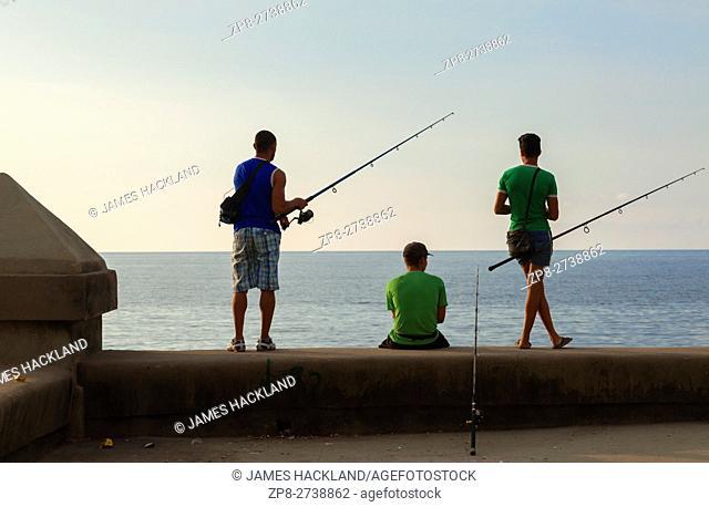 People fishing along the Malecón seawall in Central Havana, Cuba