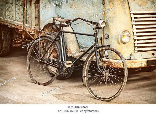 Retro styled image of an ancient bicycle and a rusty truck in a barn