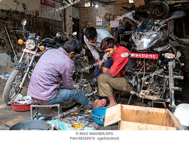 Young men work in a motorcycle workshop in the nepali capital Kathmandu.   usage worldwide. - Kathmandu/Nepal
