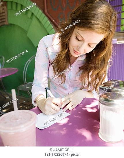 Woman writing note in outdoor cafe