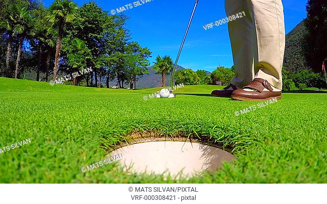 Golfer Putting the Golf Ball in the Hole on the Green in Ticino, Switzerland
