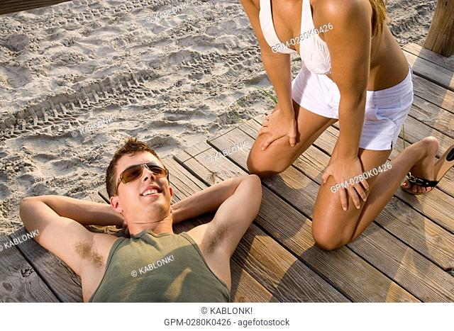 Young man lying on wooden deck at beach, woman kneeling beside