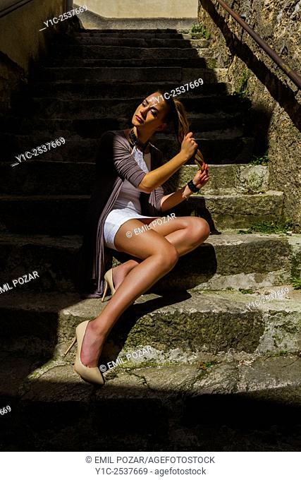 Young woman spread on stone staircase
