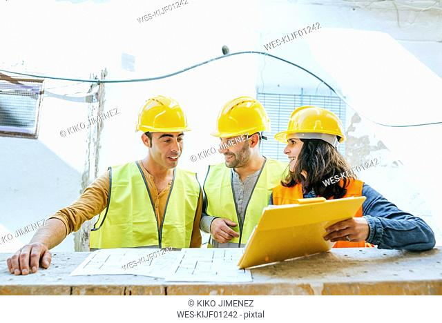 Woman showing clipboard to two construction workers on construction site