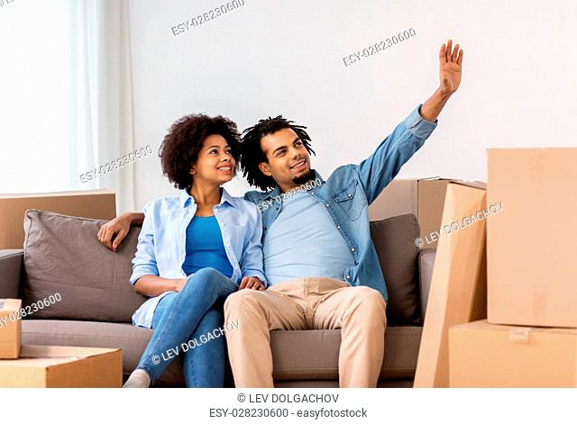 people, repair and real estate concept - smiling couple with cardboard boxes moving in or out of home