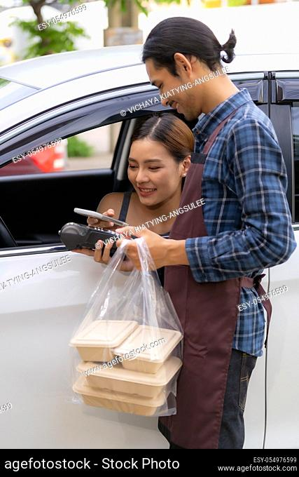 Asian woman customer make mobile payment contactless technology on drive thru food service restaurant while picking up. Drive through is new normal more popular...