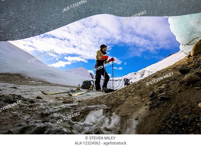 A man explores the moraine of Black Rapids Glacier on skis in the winter, viewed from a small crevice beneath the ice