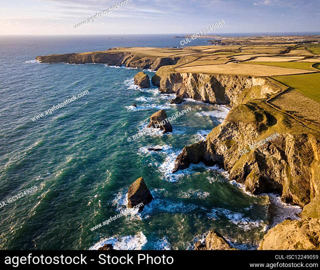 Aerial View of Bedruthan Steps in Cornwall, small secluded beach with steep cliffs and rock stacks offshore. High tide