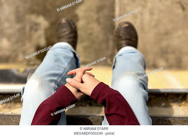 Hands and legs of woman sitting outdoors
