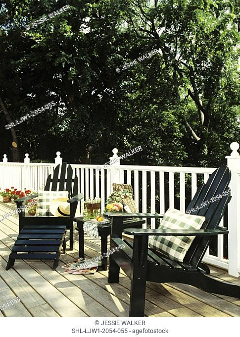 DECKS: Two dark green Adirondak Chairs sit on deck with white railing, and unstained wood deck floor, pillow and beverages set up