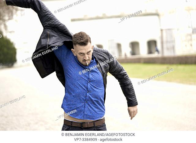 Man in blue shirt putting on Black leather jacket, Munich, Germany
