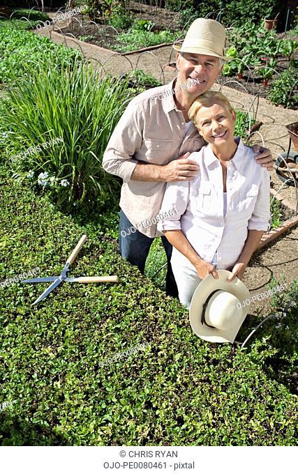 Portrait of smiling senior couple working in garden