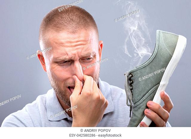 Close-up Of A Man Covering His Nose While Holding Stinky Shoe On Grey Background