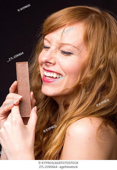 Young Redhead Woman Eating Chocolate Bar