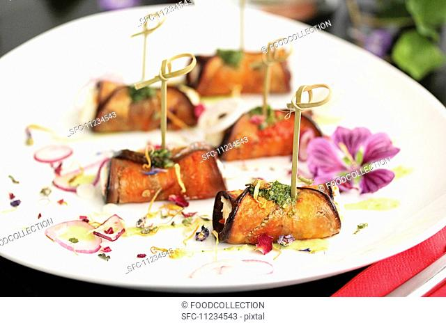 Rolled aubergine slices filled with cheese, decorated with bamboo skewers, dried flowers and slices of red onion