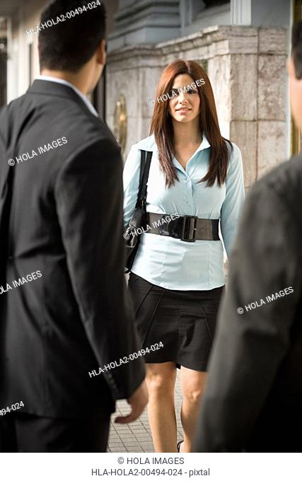 Businesswoman walking towards businessmen