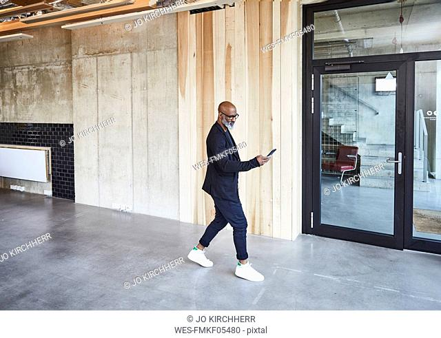 Mature businessman with cell phone walking in modern office