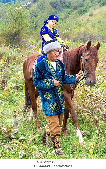 Kazakh man walking around with his son on a horse after Circumcision Sundet Toi ceremony, Kazakh ethnographic village aul Gunny, Talgar, Almaty, Kazakhstan