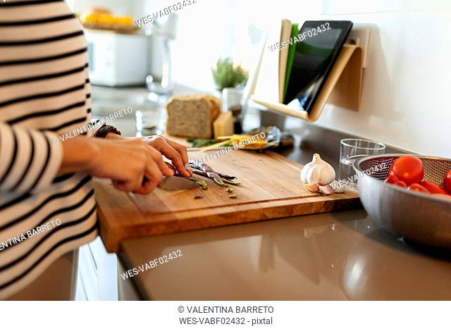 Close-up of woman cooking in kitchen at home cutting vegetables