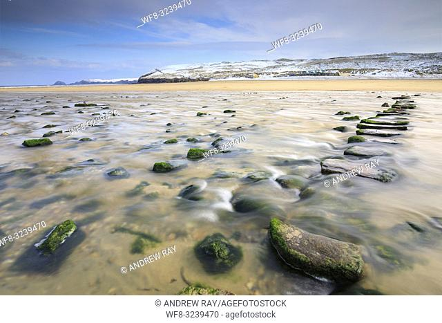 The stepping stones on Perranporth Beach on the North Coast of Cornwall, captured on a morning in mid March with snow covered sand dunes in the distance