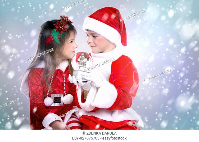 couple of children holding christmas theme ornament on snowy background