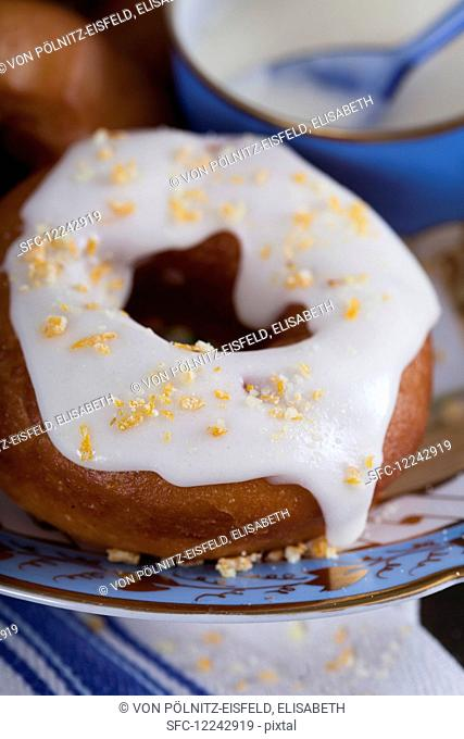 A doughnut with lemon icing and candied orange pieces