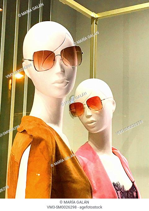Two mannequins wearing sunglasses in a shop window. Serrano street, Madrid, Spain