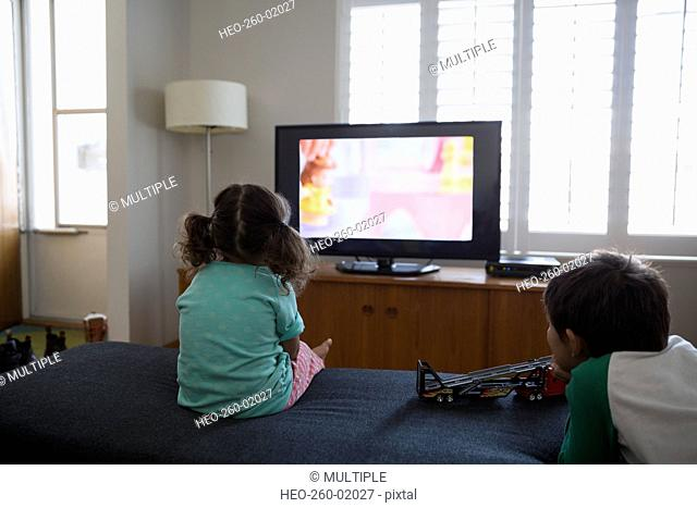 Brother and sister watching cartoons in living room