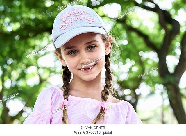 Portrait of little girl with green eyes braids and cap, smiling