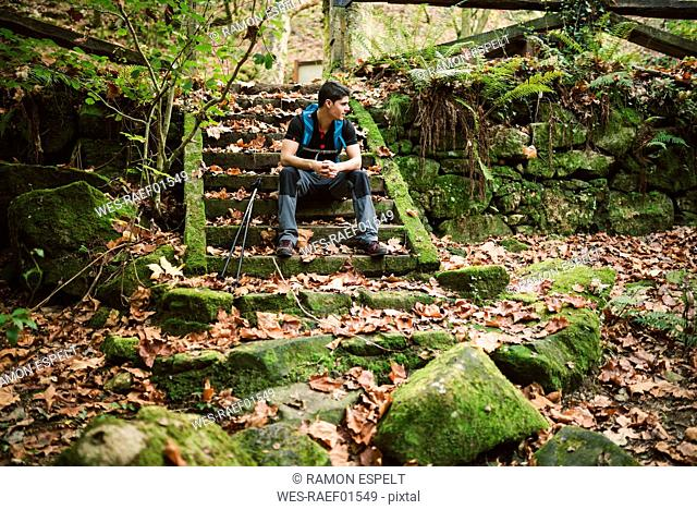 Hiker sitting on stairs having a break