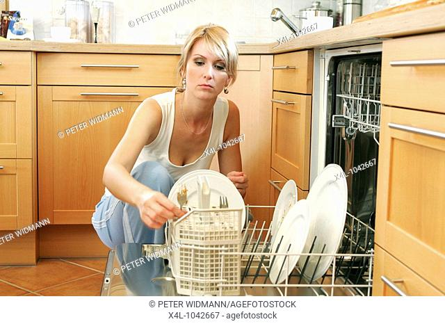 woman doing housework filling dishwasher
