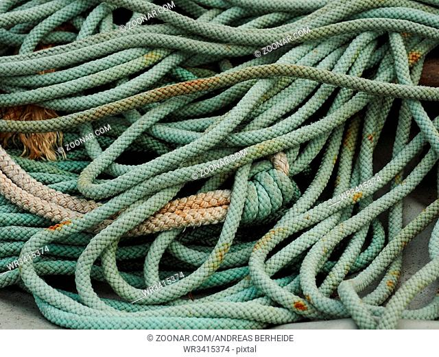 Old used green rope in a harbour, fishing equipment