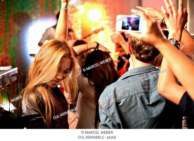 Teenagers photographing band on camera phones at concert