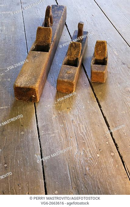 Old wooden hand planes on wooden floor in empty room inside an old 1800s cottage style home, Quebec, Canada