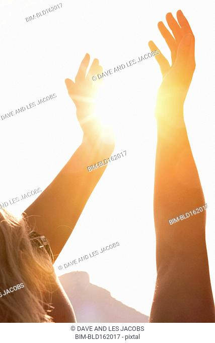 Caucasian woman holding sunshine in hands