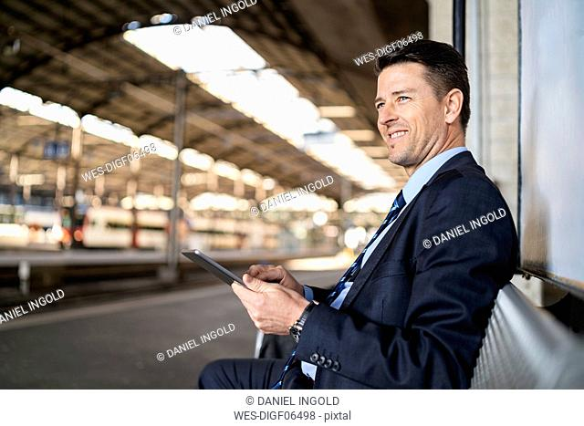 Smiling businessman with tablet waiting on station platform